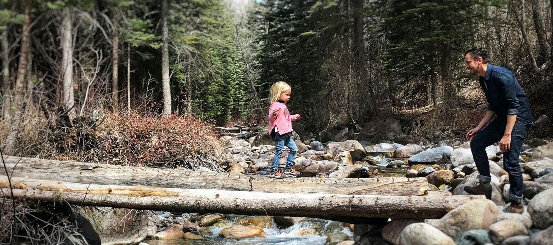 rapariga a atravessar rio andando num tronco em direção a homem de braço esticado